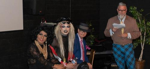 drag queens on stage with moderator at event