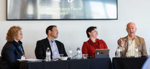 People speaking at a panel sit at tables