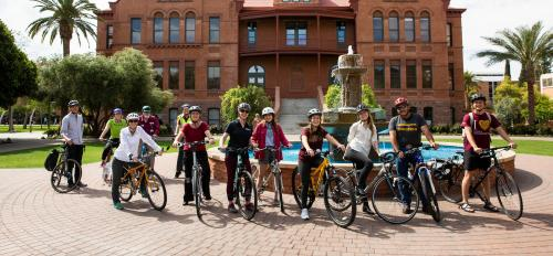 Bicyclists pose for a group photo in front of Old Main