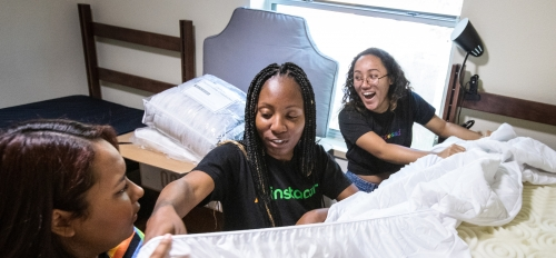 girls making a dorm bed