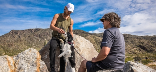 two people hiking with dog