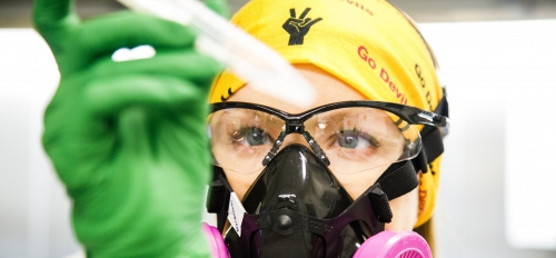 A researcher wearing a gold head cloth with ASU logos on it holds a test tube while wearing a gas mask