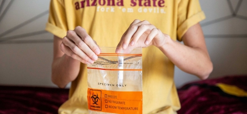 A student puts a saliva test tube into a sealable bag for COVID19 testing