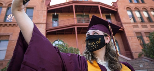 A student in graduation garb and a Class of 2020 mask takes a selfie in front of Old Main