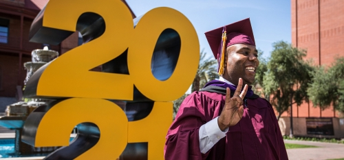 A man in a graduation cap and gown flashes the pitchfork gesture and smiles for a photo in front of a giant 2021 sign