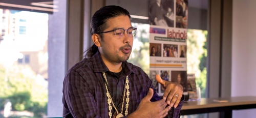 A Native American man wearing shell and bead necklaces and a plaid shirt gestures with his hands as he speaks while seated at a conference table, with a banner for the Labriola Center visible behind him