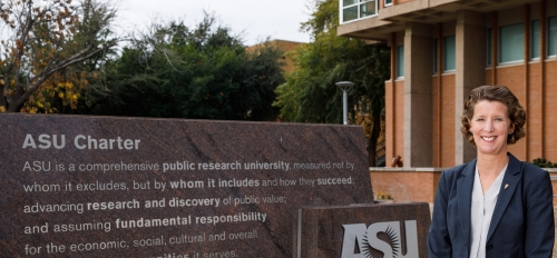 Sally Morton standing in front of ASU charter sign on Tempe campus