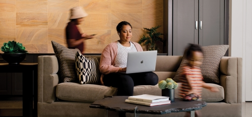 A woman works on her laptop while seated on a couch as her two children move around