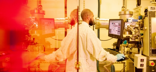 A man in a lab suit stands at a computer with semiconductor machinery behind him