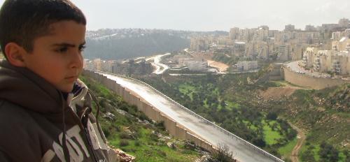 Palestinian filmmaker's son looks over at Israeli settlements from above