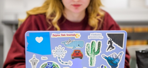A female student works on a laptop covered in ASU stickers