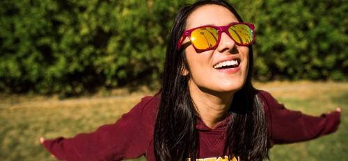 A women stands on a lawn with an ASU sweatshirt and matching sunglasses