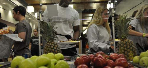 students in line dish fruit onto their plates