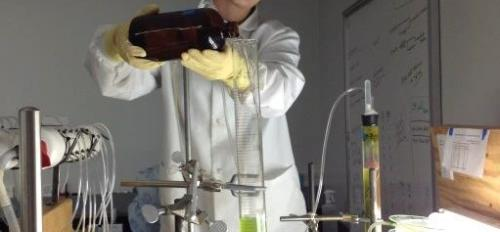 student pouring growth media into algae-filled column