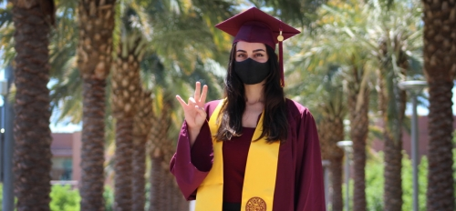 ASU graduate Almasi Sepideh wearing graduationg gown, robe, hat and face mask