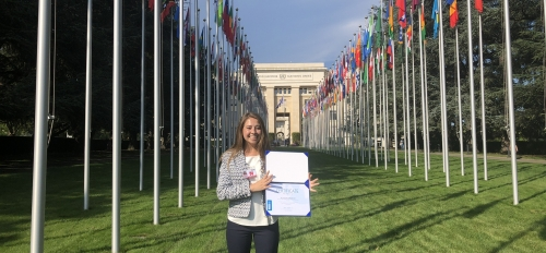 woman standing in front of United Nations flags with certificate