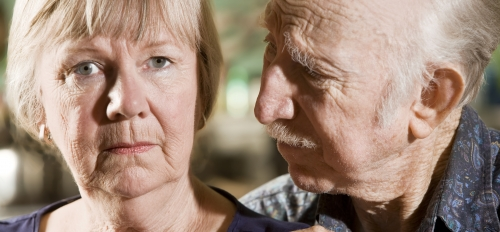older man looks at wife, who is staring out