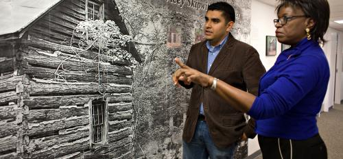 Professor Angelita Reyes converses with Jose Flores in front of mural