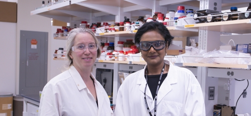 two women wearing white coats in a lab