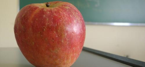 An apple sits on a teacher's desk.