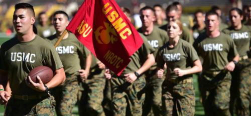 Members of the Marine ROTC run at the Salute to Service football game in 2014