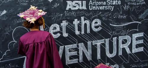 New college graduates write on a chalkboard wall