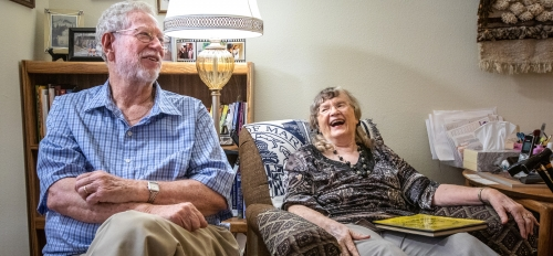 an elderly man and woman sitting in a living room laughing