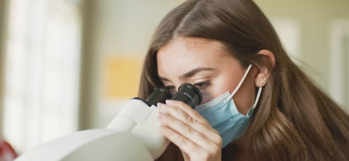 A student wearing a mask looks into a microscope