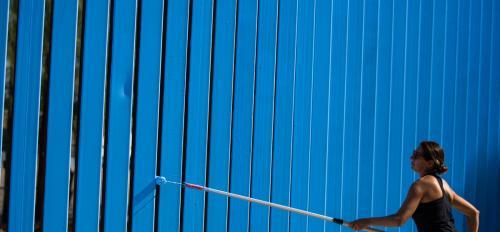 Woman painting border wall