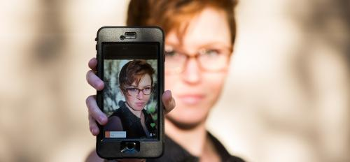 A woman holds up a phone that has her photo on it.