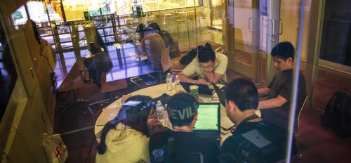 Students work around a table at a hackathon