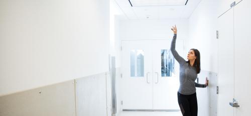 woman in dance pose in lab hallway