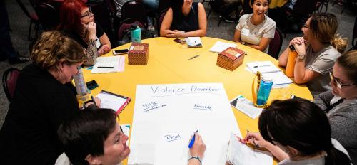 Participants at a conference on preventing domestic violence write ideas on a poster