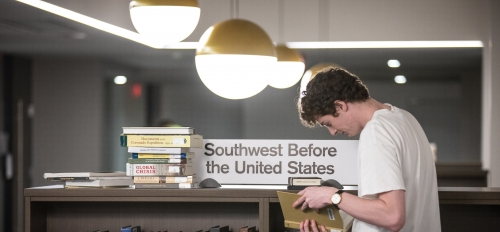 student stacking books on shelf in library