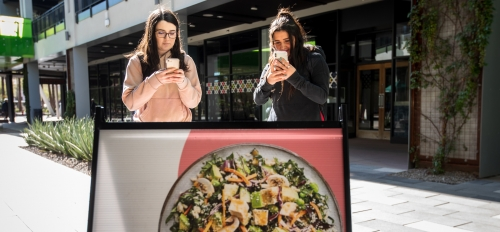 two women taking photos of a restaurant sign