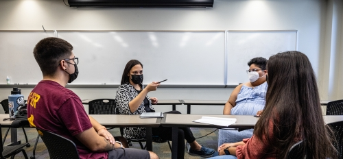 group of four people talking in classroom