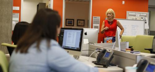 Woman in newsroom with student