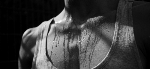 black and white close-up of person's chest with sweat on it