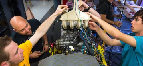 Students work on a throttle in a Formula-style race car.