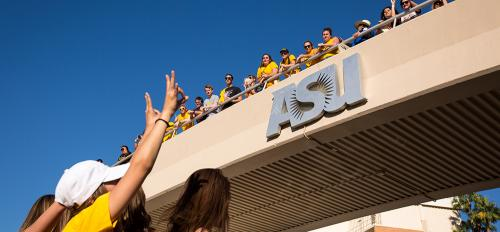 people waving from ASU bridge
