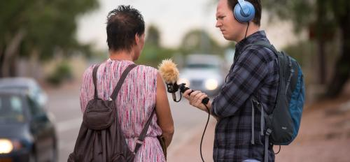 man recording a woman speaking next to a freeway