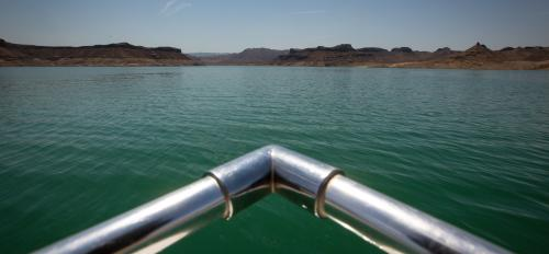 The front railing of a boat is seen above the waters of Lake Mead