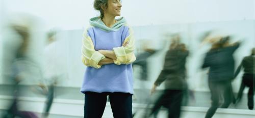 Woman standing among dancers.