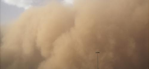 A towering cloud of dust moves through a desert city