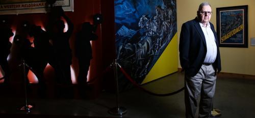 Man next to film poster