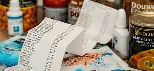 various groceries in background, receipt in foreground
