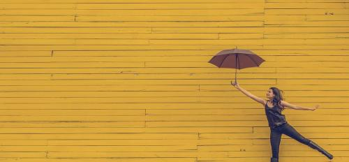 woman smiling and jumping while holding an umbrella in front of a yellow brick wall