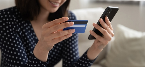 A woman uses a banking app on her smartphone.