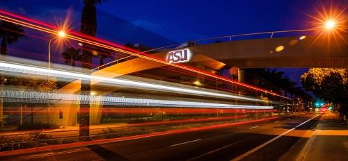 time-lapse photo of car lights going beneath ASU bridge at night