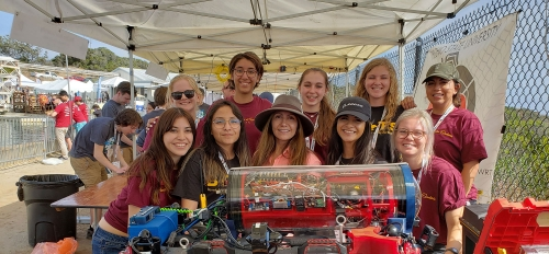 group of students posing with underwater robot